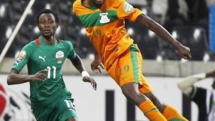 Zambia's Nathan Sinkala (R) heads the ball