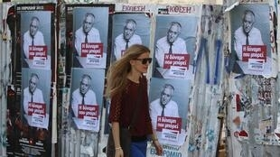 Uma mulher grega passa em frente a cartazes do Partido Democrático em Atenas, no sábado, 5 de maio.