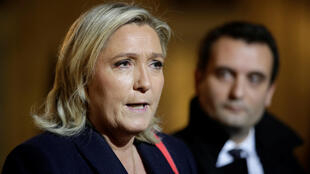 French National Front political party leader Marine Le Pen (L) speaks to journalists as party vice-president Florian Philippot (R) listens in November 2015