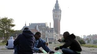Men from Eritrea and Sudan eat distributed food near Calais town hall