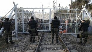 Migrants protest behind a border fence at the Greek-Macedonian border, after additional passage restrictions imposed by Macedonian authorities left hundreds of them stranded.