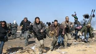 Journalists, including two New York Times photographers who are currently missing, run for cover near Ras Lanuf, 11 March 2011