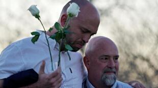 Will Beck (à esquerda), um sobrevivente do tiroteio na Escola de Ensino Médio de Columbine, abraça Lee Andres, parente de uma vítima.