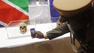 Berlin, auditorium de l'hôpital de la Charité, le 30 septembre 2011. Un membre de la délégation de Namibie prend en photo l'un des 20 crânes restitués par l'Allemagne.