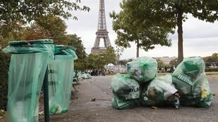 This picture taken on September 22, 2019 shows piles of garbage bags in a street with the Eiffel Tower in the background, in Paris, September 22, 2019.