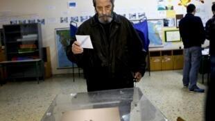 Eleitor grego vota em seção eleitoral da capital Atenas, neste domingo (25).