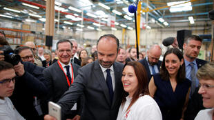 French Prime Minister Edouard Philippe (C) poses for a selfie with an employee as Junior Ecology Minister Brune Poirson (R) looks on during the visit to the the Groupe Seb Moulinex factory in Mayenne