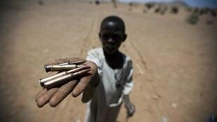 In Rounyn, in a village evacuated in north Darfur, a child shows bullet casings he found.