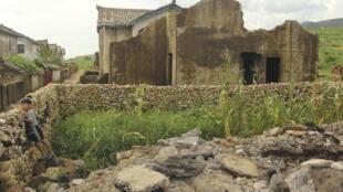 Garoto norte-coreano observa casa destruída pelo tufão que devastou o a zona rural do país, na última terça-feira