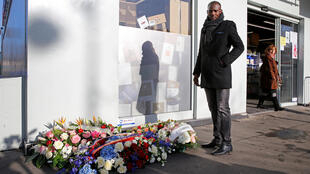 Lassana Bathily poses next to commemorative flowers outside the Hyper Casher supermarket as France pays tribute shoppers at the kosher store who were killed two years ago by an Islamist gunman in Paris, France, January 5, 2017.