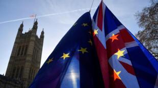 Manifestantes seguram bandeiras da UE e do Reino Unido durante um protesto anti-Brexit em frente ao Parlamento em Londres, Inglaterra, 17 de dezembro de 2018.
