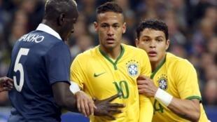 Neymar, no centro da fotografia, e Thiago Silva , na direita, disputam lance com o defesa-central francês Mamadou Sakho.