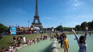 Pessoas se refrescam nas fontes do Trocadéro, em frente à Torre Eiffel, no dia 2 de agosto de 2018.