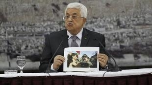 Palestinian President  Mahmoud Abbas shows a picture of minister Ziad Abu Ein, Ramallah, 10 December, 2014