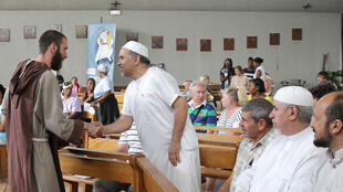 Un prêtre catholique accueille des fidèles musulmans avant une messe, à Nice.