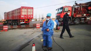Ảnh minh họa: Công nhân khử trùng một chiếc xe gần một trại nuôi lợn bị dịch tả lợn ở tỉnh Thiểm Tây (Trung Quốc). Ảnh chụp ngày 09/03/2019.