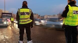 Police check cars' number plates in Paris on Tuesday