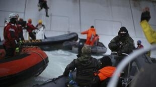 Guarda-costeira russa aborda ativistas que tentavam escalar plataforma de petróleo no Ártico.
