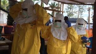 Des soignants s'équipent au centre de traitement Ebola (CTE) de Mangina dans le Nord-Kivu.