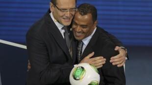 O secretário geral da Fifa, Jérôme Valcke (e) abraça Cafu durante o sorteio da Copa das Confederações, em São Paulo, neste sábado (1).