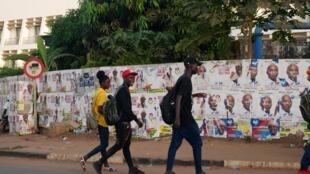 Des jeunes Bissau-Guinéens passent devant un mur recouvert d'affiches électorales, avant le premier tour de la présidentielle le 21 novembre 2019, à Bissau (image d'illustration).