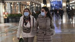 Mulheres usam máscaras nas ruas de Milão para evitar contaminação pelo coronavírus