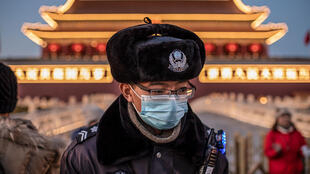 Chinese police officer in Beijing wears protective mask. The Forbidden City is closed in a bid to contain the virus during Lunar New Year celebrations.