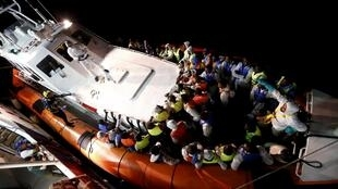 Italian coastguards bring rescued migrants ashore in Lampedusa