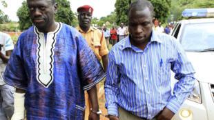 Uganda's Forum for Democratic Change leader Kizza Besigye (L) arrives handcuffed at the Nakasongola Law Court, 27 April 2011