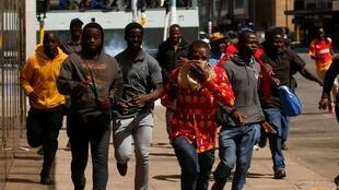 Protesters flee from teargas during clashes after police banned planned protests over austerity and rising living costs called by the opposition Movement for Democratic Change (MDC) party in Harare, Zimbabwe, August 16, 2019.