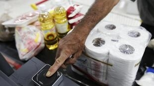 A customer puts his finger on a fingerprint scanner to buy goods in a supermarket in Caracas