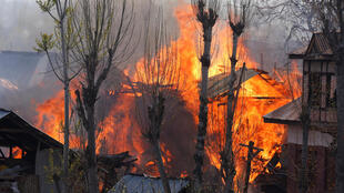 Casas incendiadas durante confronto entre soldados indianos e possíveis militantes paquistaneses, no sul de Caxemira.