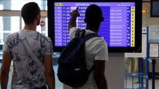 Passageiros da Air France conferem a lista de voos cancelados em Marignane, na França.