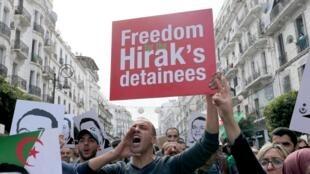 Des manifestants du Hirak brandissent des portraits du militant Ramdane Abane et demandent la libération des prisonniers du mouvement de contestation, à Alger, le 27 décembre 2019..