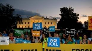 Un petit groupe d'activistes célèbrent la décision d'Obama de rejeter le projet d'oléoduc Keystone XL devant la Maison Blanche, le 6 novembre 2015.