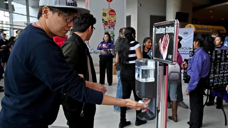 Une des stations de désinfection installées dans le Staples Center où les fans se désinfectent les mains avant d'assister à match de basketball, le 1er mars 2020.