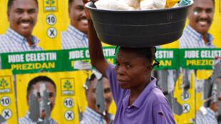 Một phụ nữ bán hàng rong bên cạnh hình của ứng cử viên Jude Celestin (Reuters)