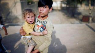 Crianças da etnia yázidi brincam em playground da região de Sinjar, onde milhares de integrantes desta minoria religiosa foram assassinados pelo grupo Estado Islâmico em 2014.