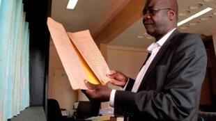 Seydouba Cissé tient dans ses mains le plus ancien document des Archives nationales.