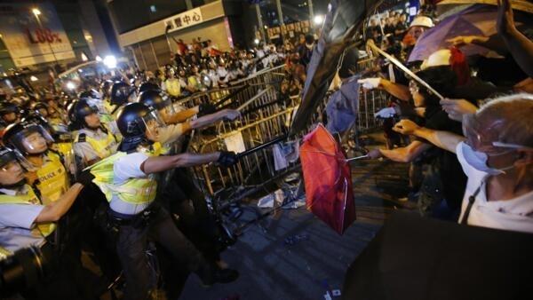 Manifestantes se defendem com guarda-chuvas, o símbolo do movimento iniciado há quatro semanas.