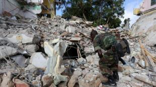 Un soldat somalien inspecte les débris suite à une attaque de shebabs à Mogadiscio (image d'illustration)
