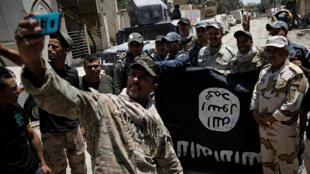 Membros do exército iraquiano com a bandeira do grupo Estado Islâmico depois de vitórias em Mossul em 17 de junho 2017.