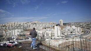 A labourer in front of the settlement known to Israelis as Har Homa and to Palestinians as Jabal Abu Ghneim