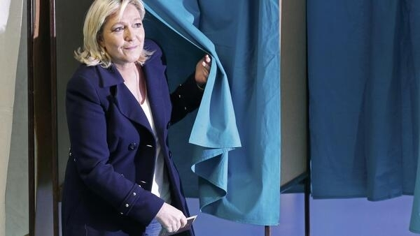 National Front leader Marine Le Pen leaves a polling booth in Henin-Beaumont