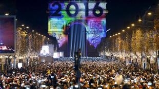 Revellers gather near the Arc de Triomphe on the Champs Elysees Avenue in Paris, France, during New Year celebrations, early January 1, 2016.