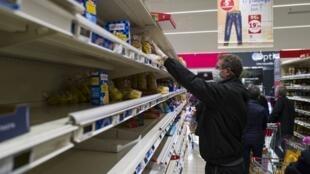 在法國東部的一家超市裡,一名戴口罩的男子在買麵食 Un homme portant un masque achète des pâtes dans un supermarché le 16 mars 2020, à Pfastatt, dans l'est de la France.