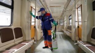 Un travailleur désinfecte une rame de métro, à Moscou, le 25 mars 2020.