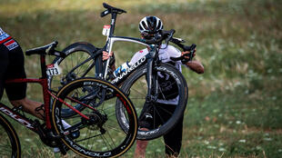 Team Sky rider Chris Froome of Britain carries his bicycle after his crash on the 201-km Stage 1 from Noirmoutier-en-l'Ile to Fontenay-le-Comte