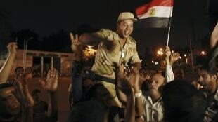 An army soldier (C) cheers with protesters, who are against Egyptian President Mohamed Morsi