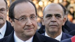 French President Francois Hollande (L) and Junior Minister for Veterans Kader Arif (R) attend a ceremony to commemorate the end of the World War One, in Oyonnax, November 11, 2013.